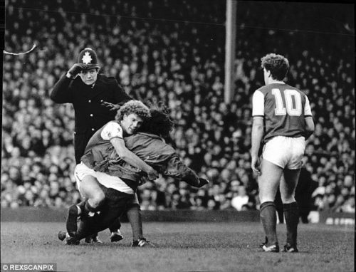 0000B4C400000C1D-2918231-Arsenal_s_Tommy_Caton_brings_down_a_spectator_invading_the_pitch-a-72_1421761295401